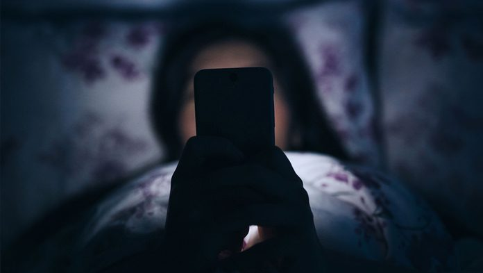 Una ragazza utilizza un device nel letto
