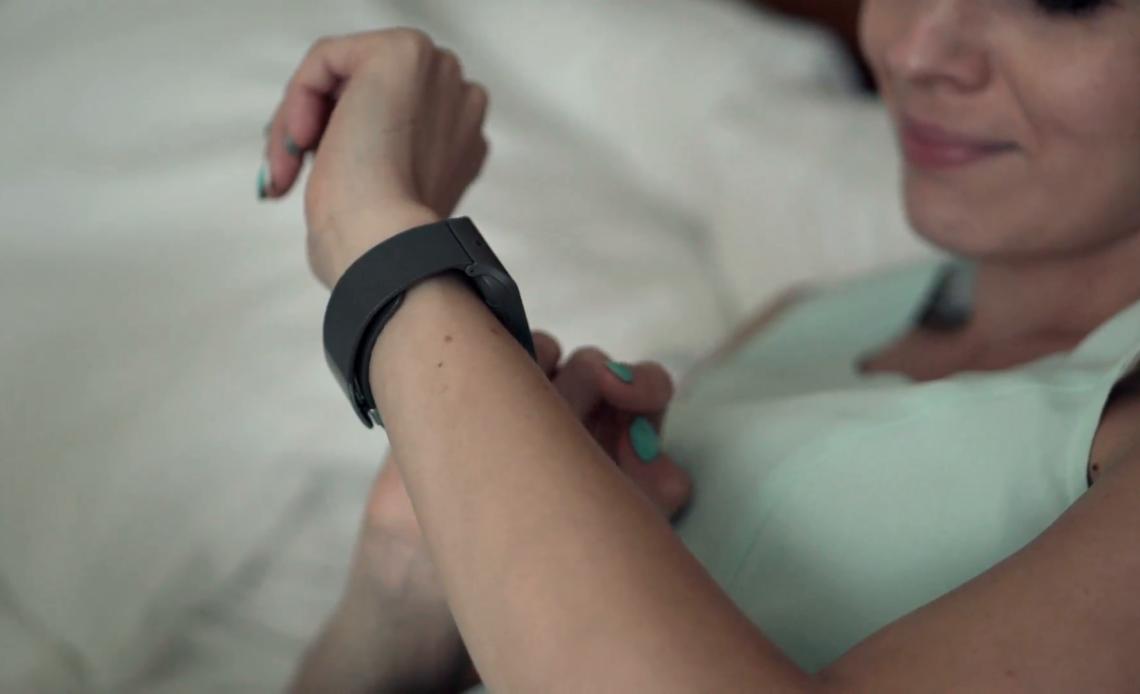 Una donna sta controllando uno smartwatch mentre è distesa in un letto.