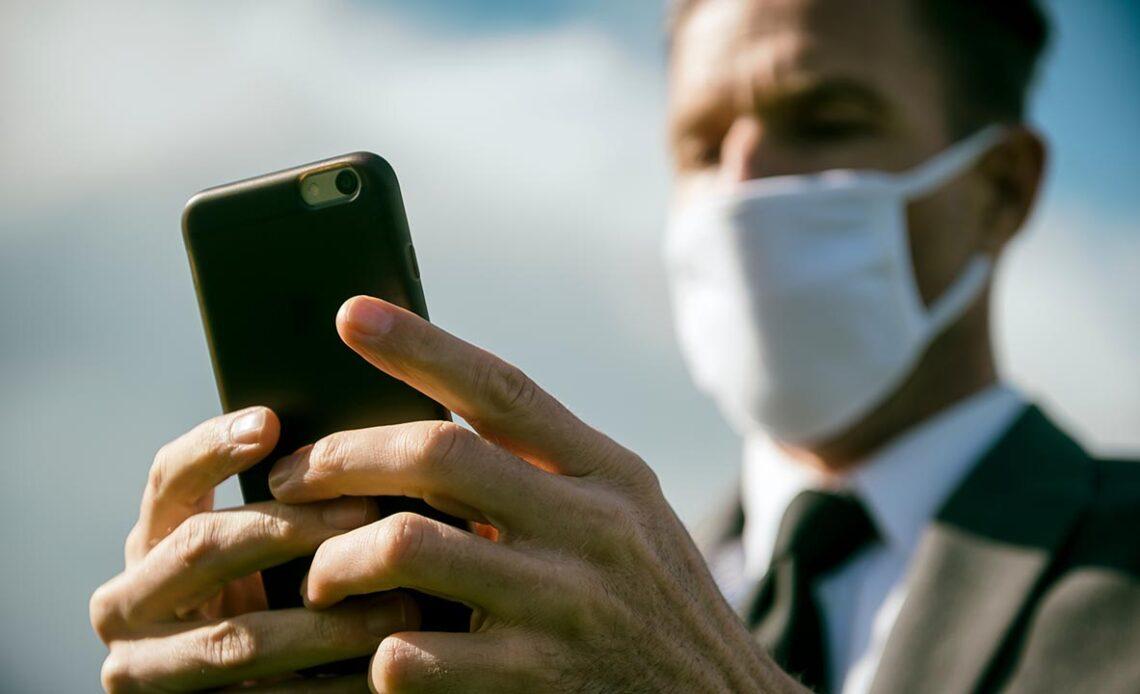 Uomo con mascherina chirurgica e smartphone