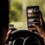 Una persona utilizza la smartphone alla guida