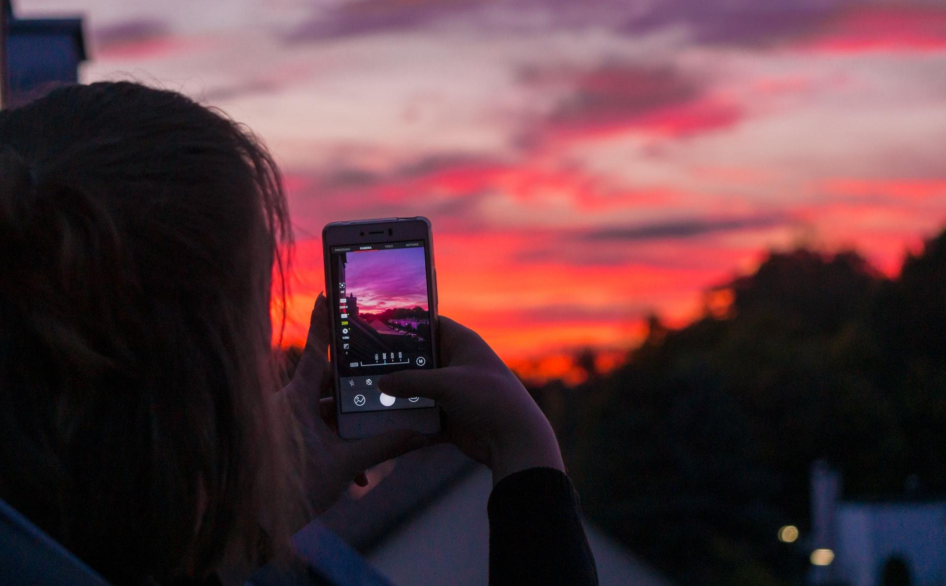 Una donna fotografa un tramonto